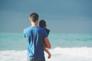 A dad holding his daughter. Both are looking out to sea.