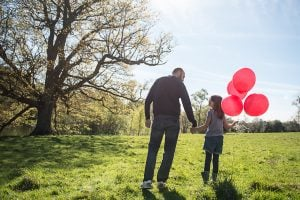 A father and daughter holding hands in the countryside. The daughter is holding 4 red balloons.
